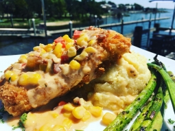 It's a perfect day in paradise! Come see us for lunch. Today's special: Chicken fried mahi over Gouda grits served with grilled asparagus and finished with cajun corn maque choux!